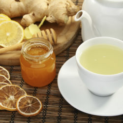 Ginger tea with honey and lemon on a bamboo napkin.
